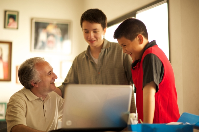 father-sons-looking-at-laptop-1080977-print